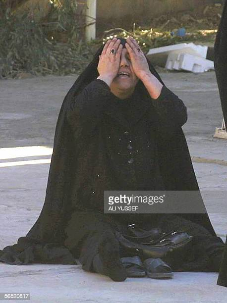A mother sits on the ground weeping after being told her 26yearold daughter a school teacher was killed in the grounds of the morgue at the general...