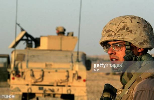A picture released by the US Marines 22 June 2006 shows a seaman looking back at an Iraqi village after sweeping through it with Marines during a...