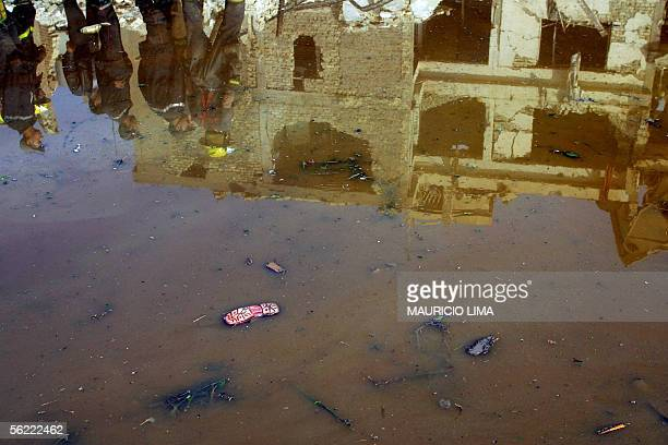 A sandal of a child appears floating in a huge puddle of water as members of Iraqi civil defense are reflected with destroyed building at the site...