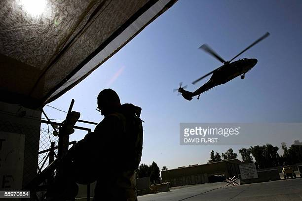 A US army soldier prepares his gear as a Blackhawk helicopter comes in for landing at a heliport in central Baghdad 20 October 2005 A senior...