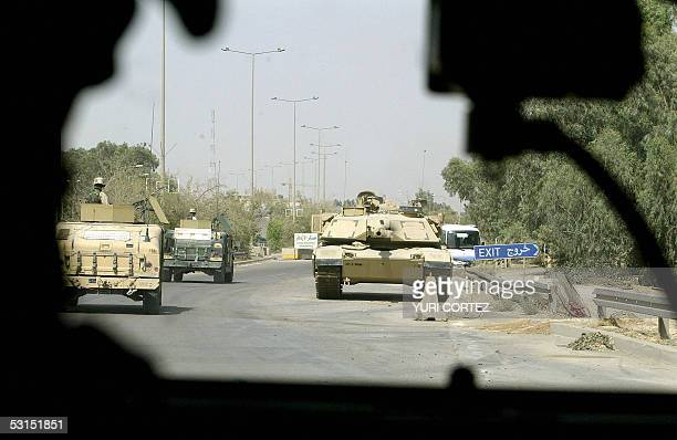 A US convoy of armored vehicles drive past near a US Abrams tank during a patrol in the hevily fortified Green Zone in central Baghdad 26 June 2005...
