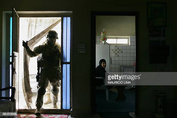 A US marine from 2nd Battalion 6th Marines Regiment enters a house to search as an elderly Iraqi woman in seen inside a kitchen during a foot patrol...