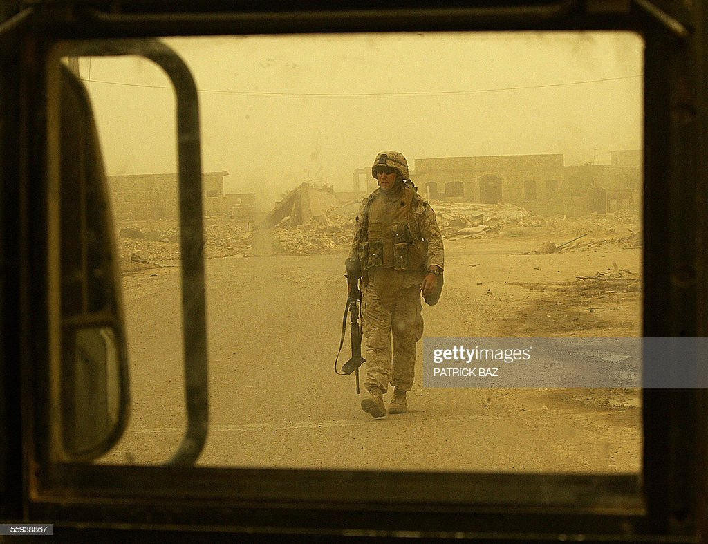 A US marine from the 6th Civil Affairs Group (CAG) with the 6th Marine Expeditionary Force (MEF) is seen through the bullet proof window of a Humvee as he checks an alley for a possible Improvised Explosive Device (IED) during a sandstorm in the city of Fallujah, west of Baghdad, 17 October 2005. More than 60 percent of the population returned to the city devastated by heavy combats between US marines and insurgents in November 2004. About 70 insurgents were killed in US air strikes in the Ramadi region of western Iraq, where five US and two Iraqi soldiers were killed in a weekend roadside bombing, the US military said today.