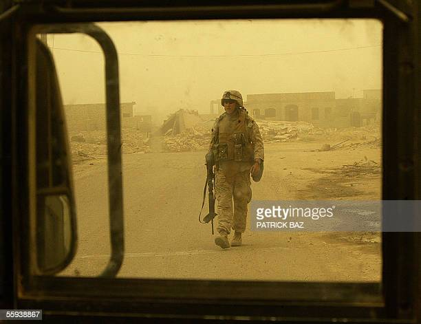 A US marine from the 6th Civil Affairs Group with the 6th Marine Expeditionary Force is seen through the bullet proof window of a Humvee as he checks...