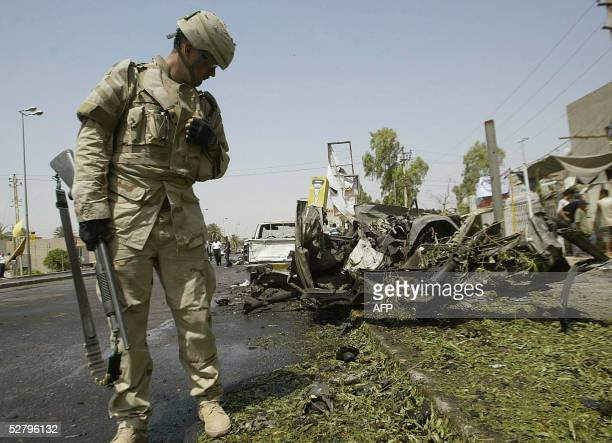 A US soldider looks at debris strewn at the site of a suicide car bomb explosion in alMansour district west of Baghdad 11 May 2005 At least 64 people...