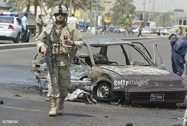 A US soldider secures the site of a suicide car bomb explosion in alMansour district west of Baghdad 11 May 2005 At least 64 people were killed in a...
