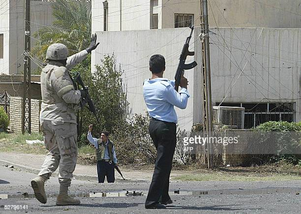 A US soldier and Iraqi policemen secure the site of a suicide car bomb explosion in alMansour district west of Baghdad 11 May 2005 At least 64 people...