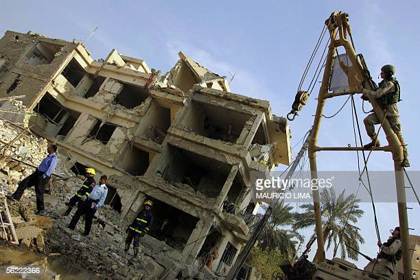 A US soldier from 464 Battalion 3rd Infantry Division prepares a crane to lift rubble of a destroyed building at the site where two suicide bombers...
