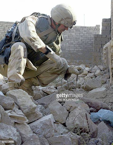 A US Soldier from the Bomb Squad of the First Battalion 17th Regiment sets up an explosive next to an abandoned mortar shell found un a Christian...