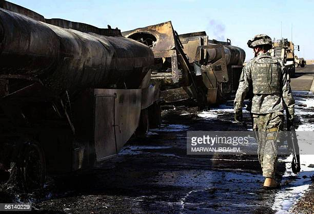 A US soldier inspects the wreckage of petrol tanks that were destroyed in an attack in the outskirts in the city of Kirkuk 11 November 2005 The...