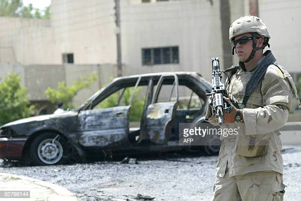 A US soldier secures the site of a suicide car bomb explosion in alMansour district west of Baghdad 11 May 2005 At least 64 people were killed in a...