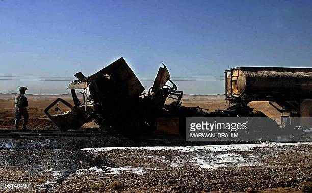 A US soldier secures the wreckage of petrol tanks that were destroyed in an attack in the outskirts in the city of Kirkuk 11 November 2005 The attack...