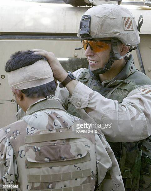 A US soldier wraps the head of a wounded Iraqi soldier with a bandage following a suicide attack in the central Karrada district of Baghdad 24...