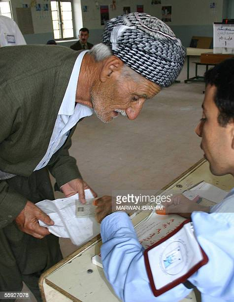 An employee of the Independent Electoral Commission in Iraq helps an old Kurdish man at a polling station in the city of Kirkuk north of Baghdad 15...