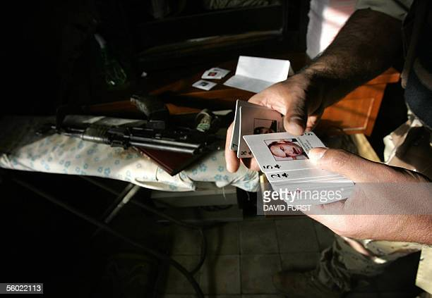 An Iraqi army soldier inspects a deck of cards with pictures of the US military's most wanted men in Iraq found during a joint search operation with...