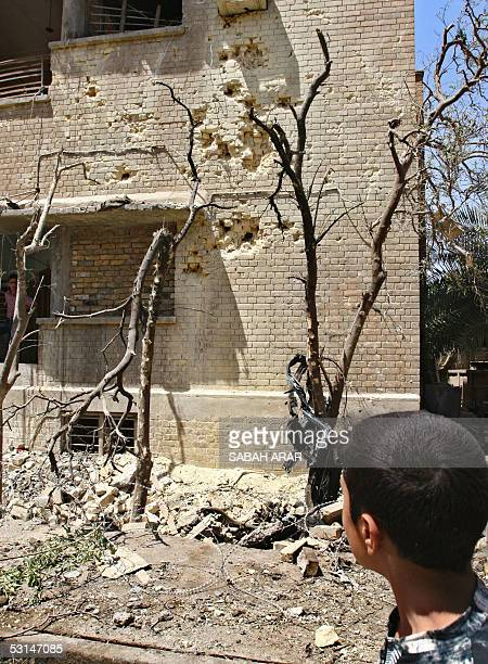 An Iraqi boy looks 25 June 2005 at damage caused by a car bomb attack few days ago in Karrada area in central Baghdad The new Iraq is still a place...