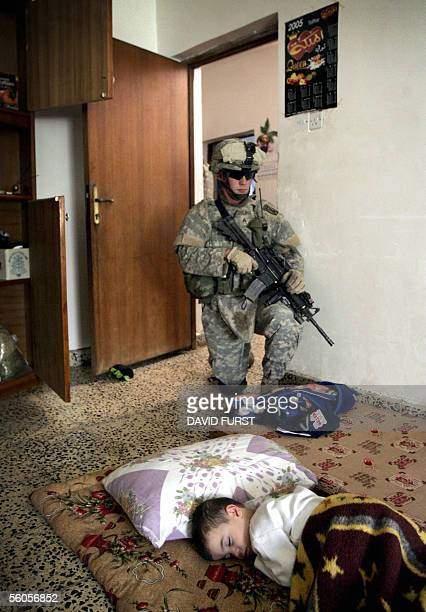 An Iraqi boy sleeps on the floor as a US soldier from Bravo Company 187 Infantry 10th Mountain Division 1st Brigade Combat Team guards a doorway...