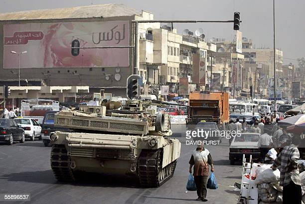 An Iraqi civilian carrying plastic bags walks past a US army tank from the 164 3rd infantry division stuck in traffic on a main road during a patrol...