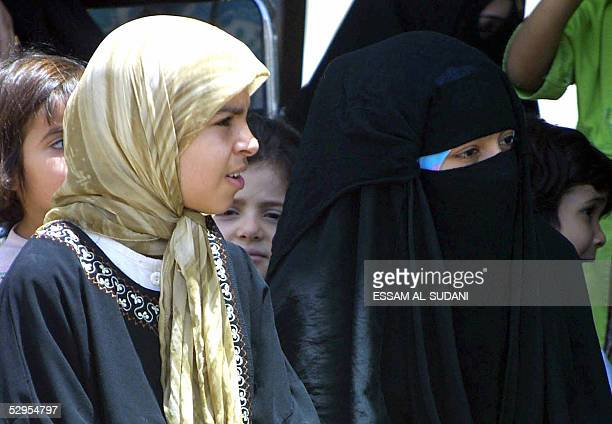 An Iraqi girl sits with other adult women in the female section of the mosque during Friday noon prayers at a mosque in the southern city of Basra...