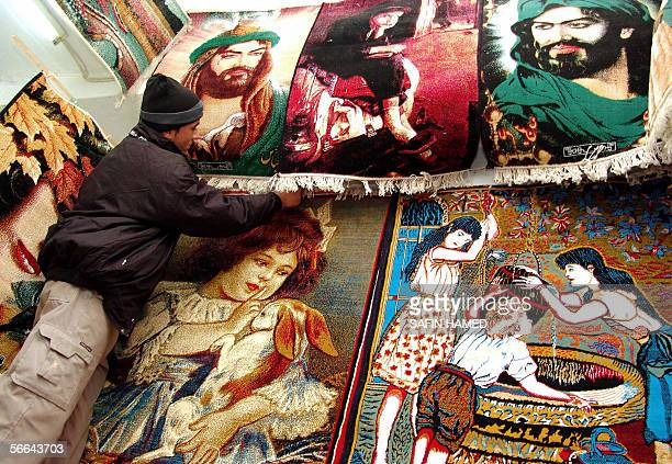 An Iraqi Kurdish man sells carpets bearing images of Imam Ali cousin of Prophet Mohammed and his son Imam Hussein at a market in Arbil 350 kms north...