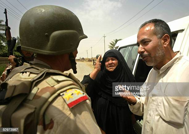An Iraqi man and his wife speak with the Brigadier General Aziz Swady commander of Iraqi alMuthana Brigade as he goes on foot patrol with his...