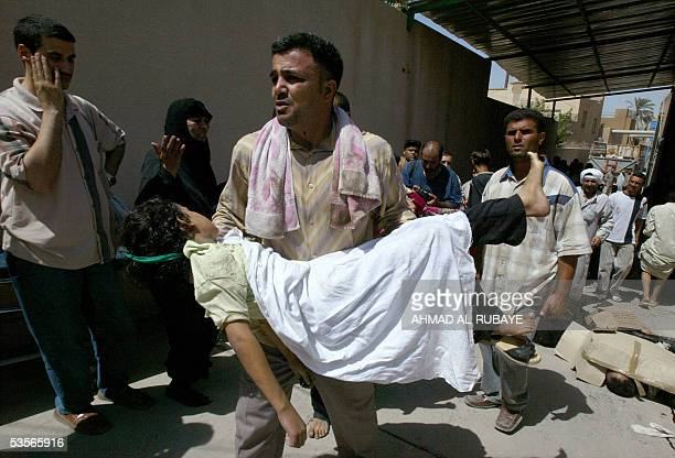 An Iraqi man carries the body of a young girl following a stampede on a bridge in Baghdad 31 August 2005 More than 630 people were killed in a...