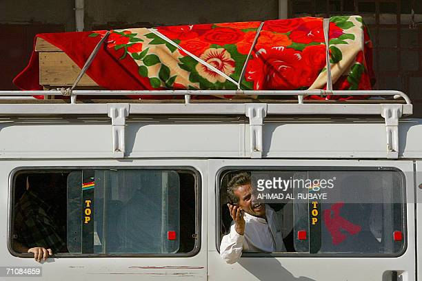 An Iraqi man mourns his relative as he sits in a minibus carrying the coffin on its top in the town of Husseiniya 31 May 2006 Twentytwo Iraqis were...