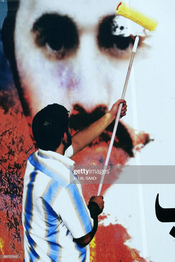 An Iraqi man paints over the picture of : News Photo