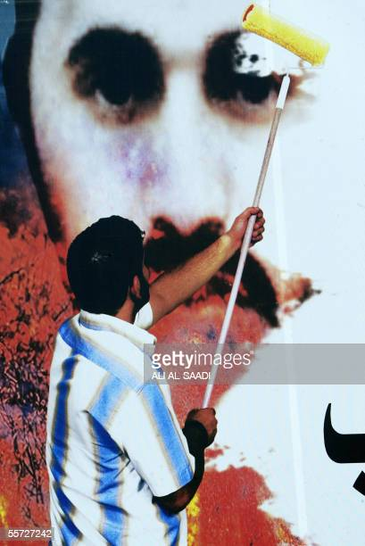 An Iraqi man paints over the picture of AlQaeda's frontman in Iraq Abu Musab alZarqawi on a billboard in Baghdad 20 September 2005 Zarqawi called for...