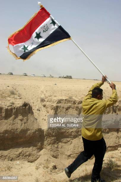 An Iraqi man runs with the national flag during a protest against a barrier put up by Kuwait south of the town of Umm alQasr close to the city of...