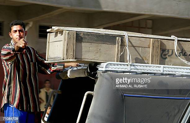 An Iraqi man stands on the back of a minibus as the coffin of a relative is carried on its top in the town of Husseiniya 31 May 2006 Twentytwo Iraqis...