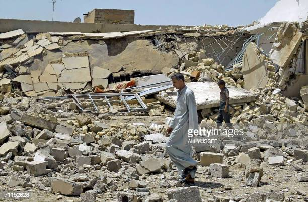 An Iraqi man walks 08 June 2006 in front of one of four houses believed to be destroyed by US forces in the town of Hibhib north of the restive of...