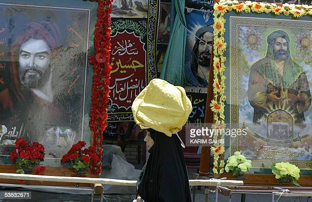 An Iraqi pilgrim walks past decorated images of Shiite Muslim Imam Hussein Imam Abbas and Imam Ali as she arrives to the Imam Kazem shrine located at...