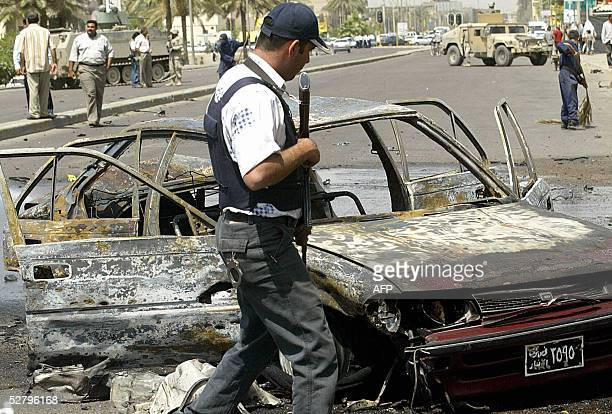 An Iraqi policeman secures the site of a suicide car bomb explosion in alMansour district west of Baghdad 11 May 2005At least 64 people were killed...