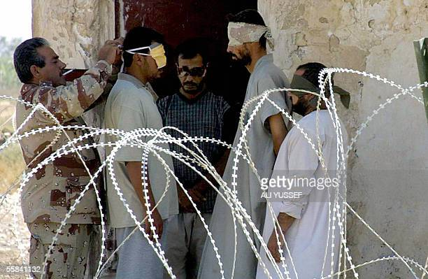 An Iraqi soldier adjusts the blindfold of a detained suspect at his base in the city of Baquba northeast of Baghdad 03 October 2005 The Iraqi army...