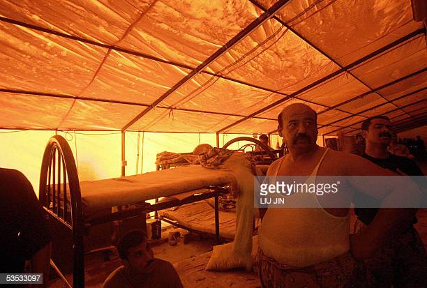 An Iraqi soldier of the 1st Battalion 5th Brigade 6th Division fans himself using a towel in a tent with a broken airconditioner at a army camp in...