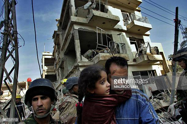 An Iraqi takes away his daughter from their collapsed apartment building that was partially destroyed at the site where two suicide bombers detonated...