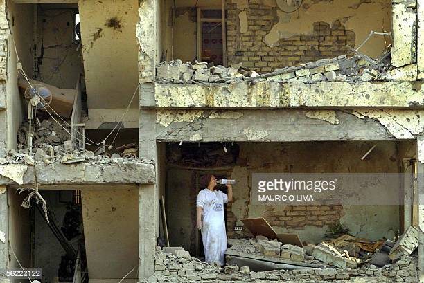 An Iraqi woman drinks water as she tries to rescue personal belongings inside her collapsed apartment at the site where two suicide bombers detonated...