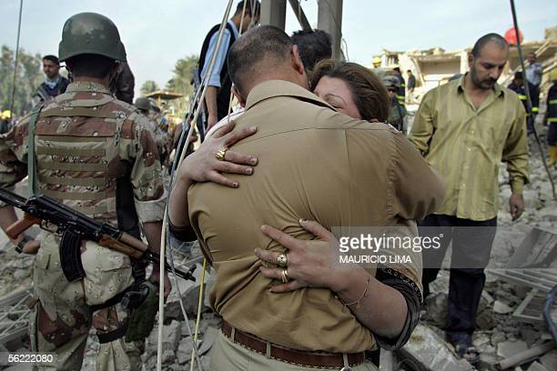 An Iraqi woman hugs her husband at the site where two suicide bombers detonated explosivesladen cars near Al Hamra hotel that houses foreign...