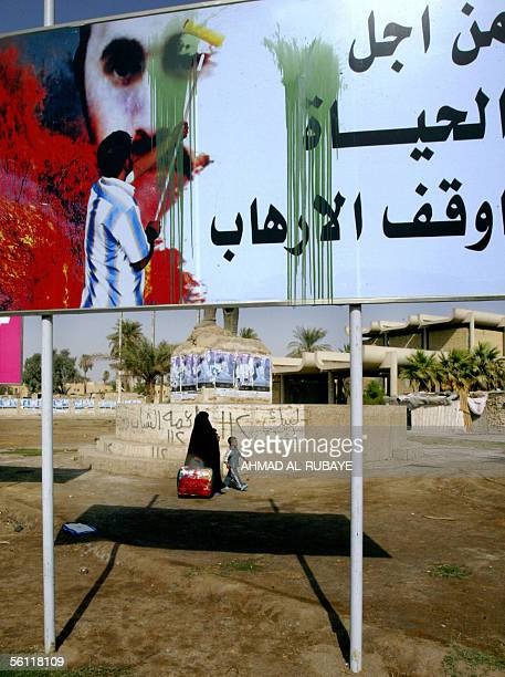 An Iraqi woman walks behind a billboard showing a man painting the face of alQaeda's Iraq front man Abu Musab alZarqawi and a slogan that reads For...