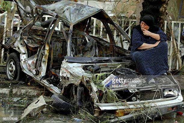 An Iraqi woman weeps as she sits on the wreckage of a burned at the site where two suicide bombers detonated explosivesladen cars near Al Hamra hotel...