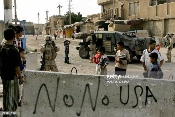 An US soldier from 1st Battalion 184th Infantry Regiment takes a snapshot of antiamerican graffiti painted on a concrete block in the Sunni AlDura...