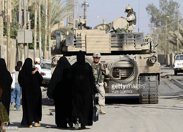 An US soldier member of Charlie Company BN 37 Infantry looks towards Iraqi women walking towards a M1 US Abrams tank in AlRay neighbourhood during a...