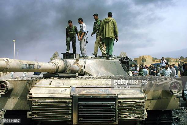 Iraq, Baghdad: Men on a destroyed tank. In the background: clouds of smoke.