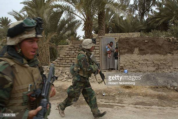 Iraq civilians watch as U.S. Marines of the 1st Marine Division jog past through a street March 30, 2003 of Tahrir, Iraq, which is approximately 100...