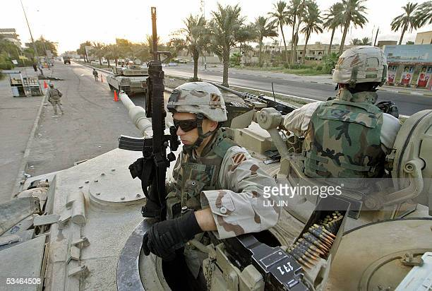 Crew members of US M1 Abrams Tank of Delta Company of Task Force 464 Armor guard on their gunner positons during a Traffic Control Point mission as...