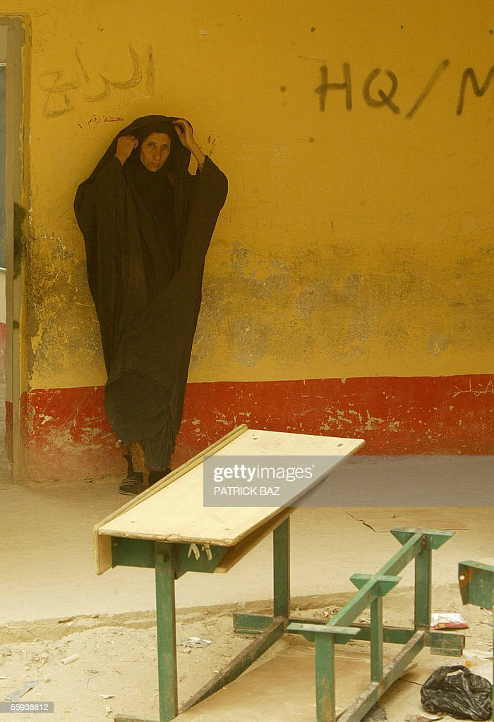 In the midst of a sand storm that engulfed Iraq, an Iraqi school teacher fixes her veil before entering her classroom in the city of Fallujah, west of Baghdad, 17 October 2005. More than 60 percent of the population returned to the city devastated by heavy combats between US marines and insurgents in November 2004. About 70 insurgents were killed in US air strikes in the Ramadi region of western Iraq, where five US and two Iraqi soldiers were killed in a weekend roadside bombing, the US military said today.