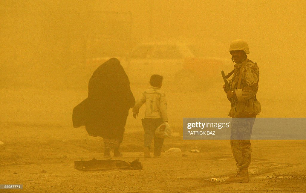 In the midst of a sand storm that engulfed Iraq an Iraqi woman and her son walk past an Iraqi army soldier manning a roadblock in the city of Fallujah, west of Baghdad, 17 October 2005. More than 60 percent of the population returned to the city devastated by heavy combats between US marines and insurgents in November 2004. About 70 insurgents were killed in US air strikes in the Ramadi region of western Iraq, where five US and two Iraqi soldiers were killed in a weekend roadside bombing, the US military said today.