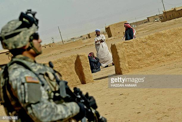Iraq men look at US soldiers patrolling the northern village of Sakar near the Syrian border 04 April 2006 Iraqi leaders shelved talks on forming a...