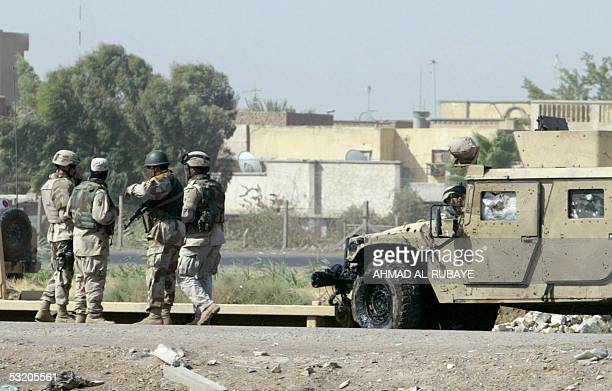 Iraqi and US soldier gather near a US Humvee that was damaged in a roadside bomb explosion east Baghdad 07 July 2005 Two US soldiers were wounded in...